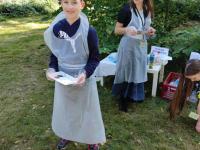 Młody uczestnik Malowania naNarodowe Czytanie ubrany wfartuszek trzymający farby.