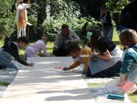 Mieszkańcy malujący podługim arkuszu ztektury.
