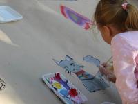 Dziewczynka maluje kota natekturze.